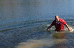 "Head coach Ryan Banta jumps into a lake at Engler Park om Farmington immediately following the four girls, junior Sarah Madsen and Sophomores Richelle Bain, Lizzie DeJoie and Claire Huang, qualifying for State. ""If all four of you girls qualify I will go run in that lake and take a dive, rather a nice little plunge, into the water,"" Banta said. ""It was rather cold. It was kind of like an ice bucket challenge."" Photo courtesy of Richelle Bain."
