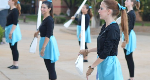 "Junior Jennifer Wayland practices rifle spinning prior to the home football game on Sept. 26. The color guard began using rifles under director Liz Bryan. ""A rifle is a much stronger technique used,"" Bryan said. ""Because it is a smaller equipment, you have to have more control over it."" Photo by The Corral."