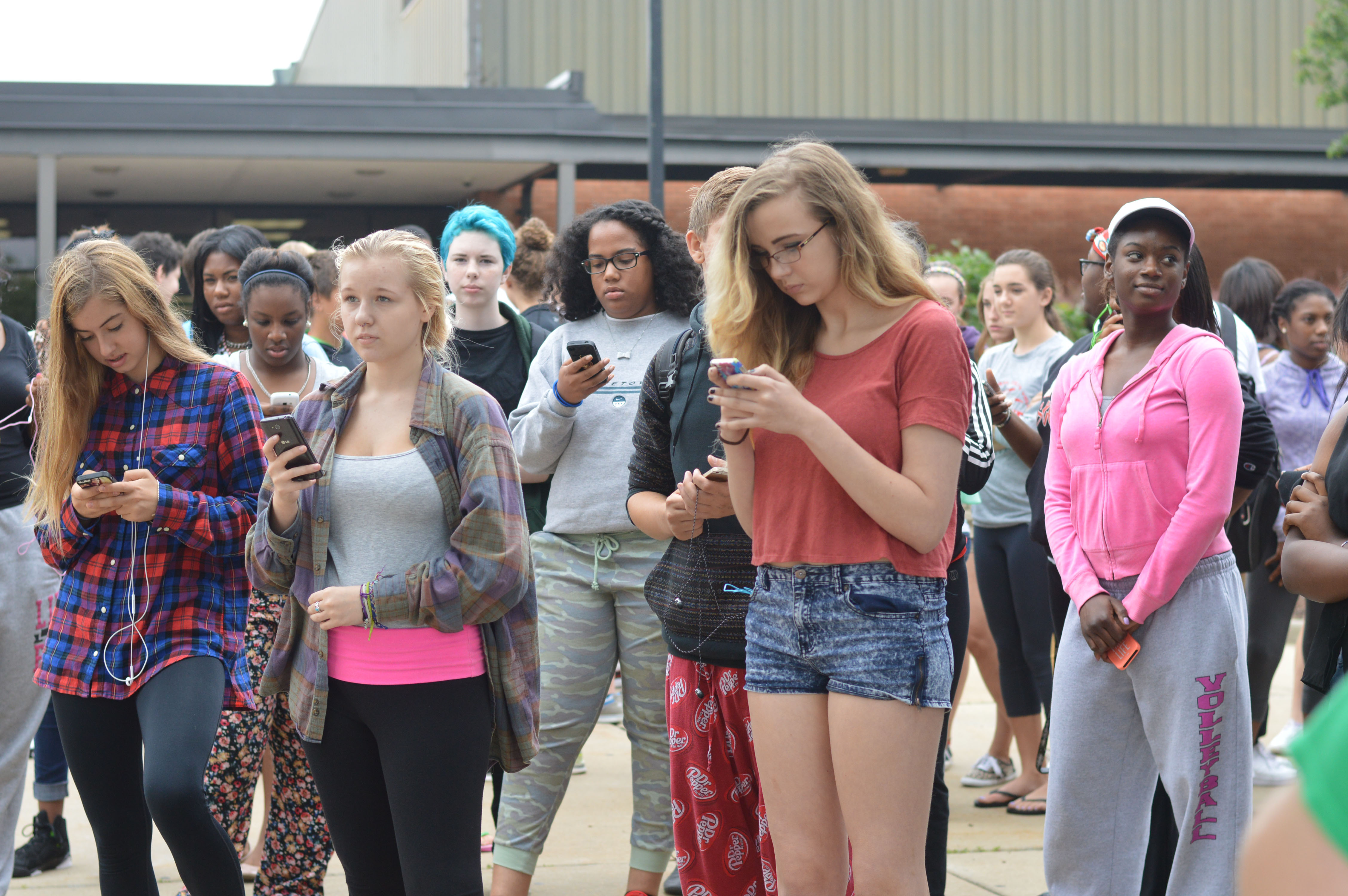 A group of protesters stand on their phones during the first walkout held on Sept. 10, outside of school by the flag pole. Students posted words of support on Twitter and Vines of the walkout on social media. Photo by Piper Rother.