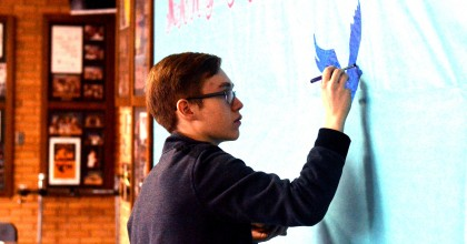 "Junior Matthew Kertzman paints the lobby display publicizing the upcoming musical,""Mary Poppins"".  The show opens Feb. 26.  Photo by Matt Frischer."