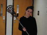 Carly Lander holding her lacrosse stick. Photo by Ben Kraizer